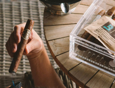 Hand holding lit cigar and humidor with boveda