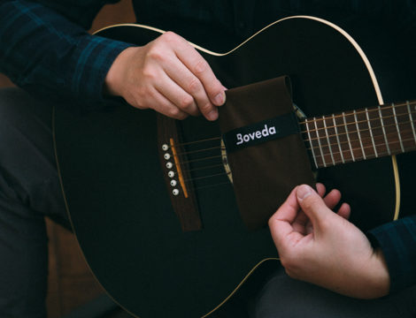 Man holding a Guitar and a Boveda pack.