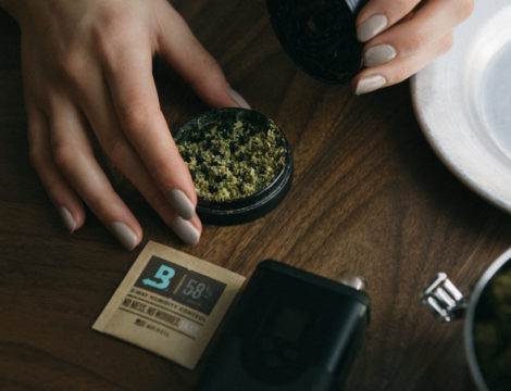 Boveda pack and a grinder with ground flower