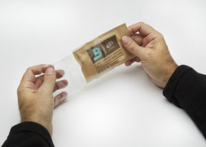 Hand removing 49% RH Boveda from the plastic wrapper